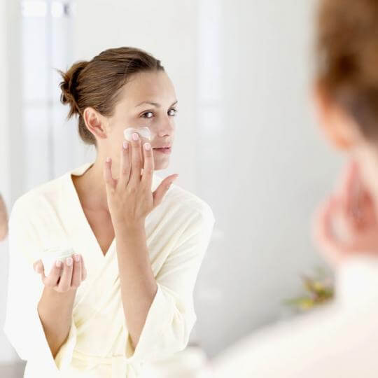 Woman Using Moisturizer